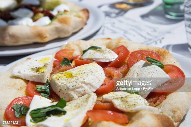 Close-Up Of Caprese Salad Pizza Served In Plate On Table