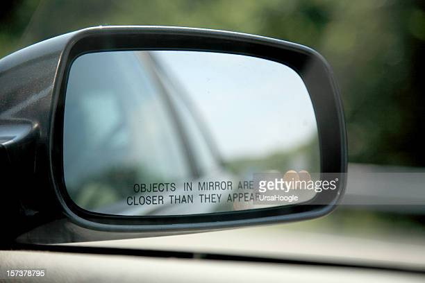 Close-up of car mirror objects are closer than they appear