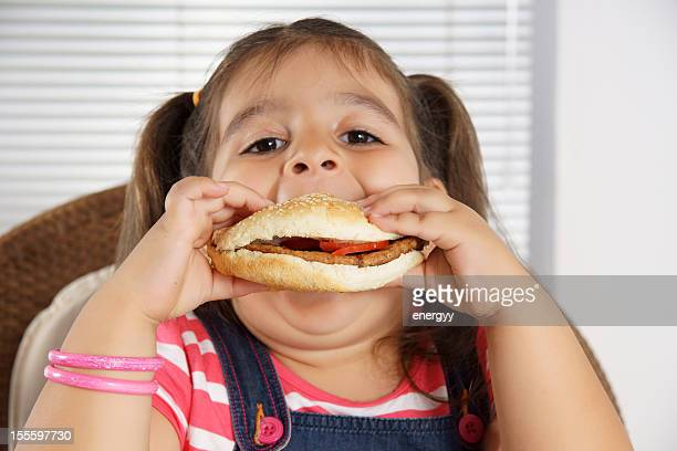 Close-up of Caucasian girl with pigtails eating a burger
