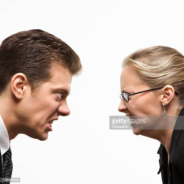 Close-up of Caucasian mid-adult man and woman staring at each other with hostile expressions.