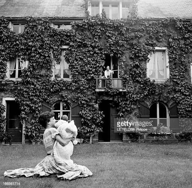 CloseUp Of Cecile Aubry And Son Mehdi En France en juin 1956 portrait de Cécile AUBRY les cheveux courts assis dans l'herbe d'un jardin devant une...