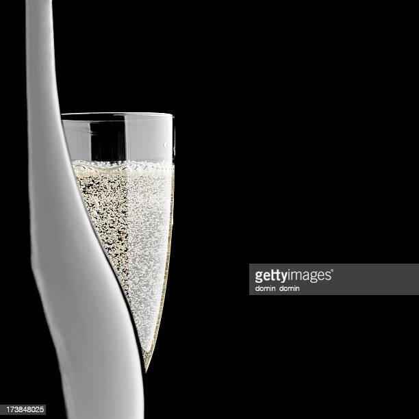 Close-up of champagne bottle and glass, isolated on black background