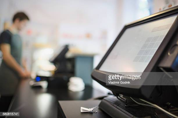 Close-up of checkout counter with cashier in background at coffee shop