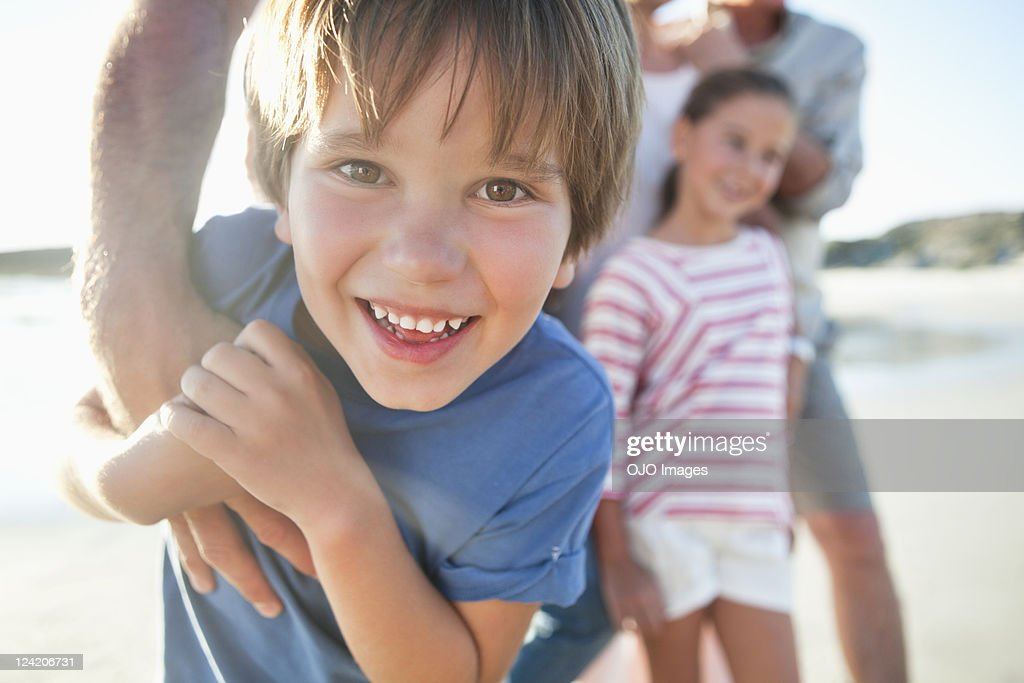 Close-up of cheerful boy on a beach enjoying with family : Stock Photo