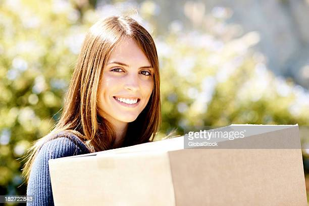 Close-up of cheerful woman carrying a box while shifting house
