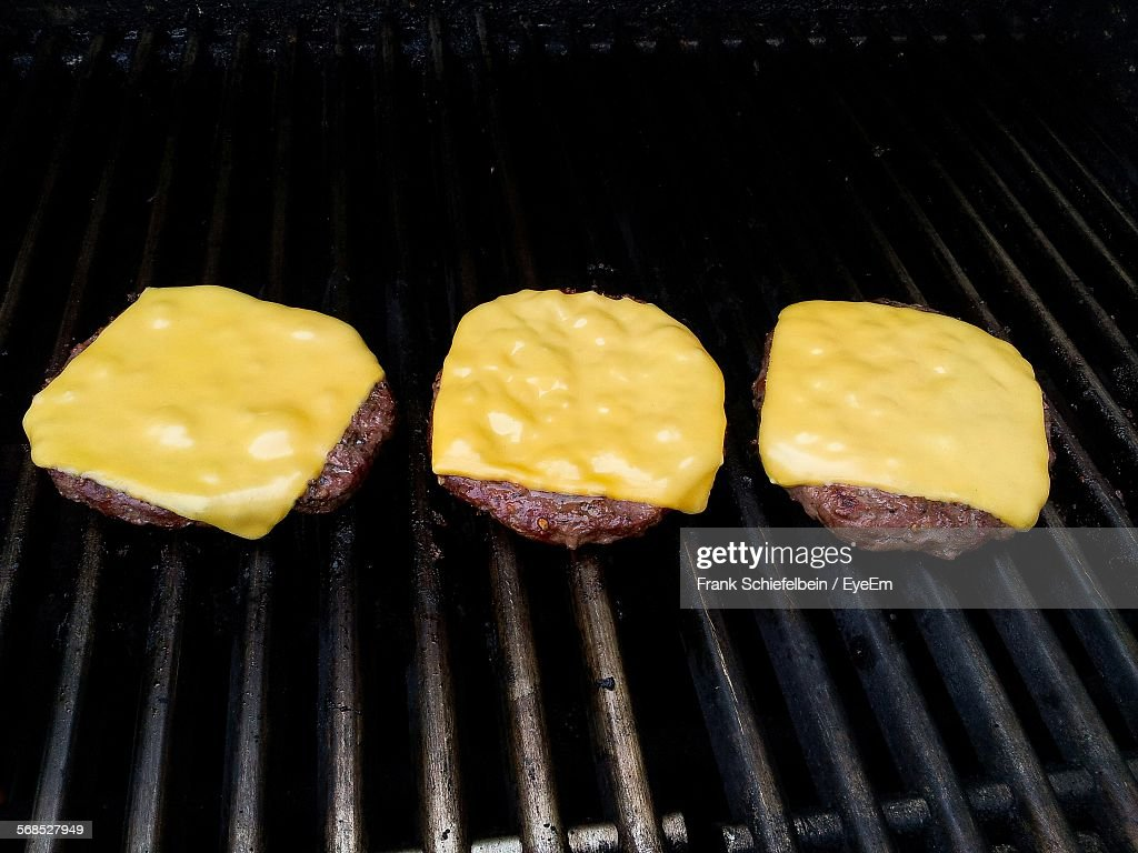 Close-Up Of Cheese Hamburger On Barbecue Grill