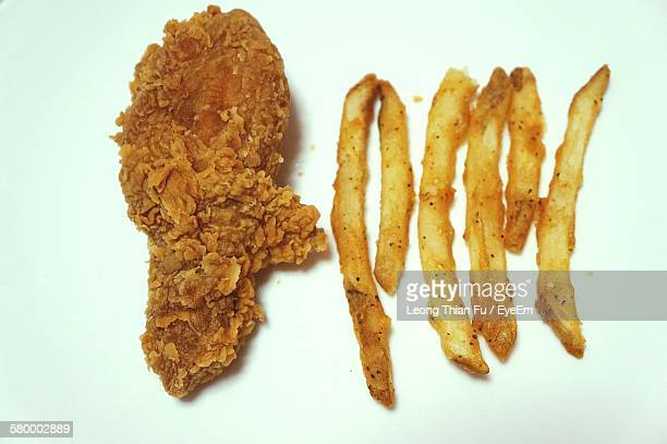 Close-Up Of Chicken And French Fries Against White Background