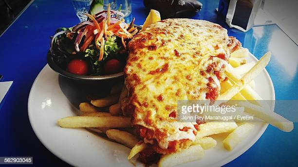 Close-Up Of Chicken Parmigiana With French Fries Served On Table