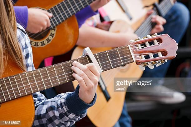 Close-up di bambini Suona la chitarra acustica all'aperto, poco profonde DOF