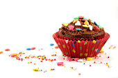Close-Up Of Chocolate Cupcake With Sprinkles Against White Background