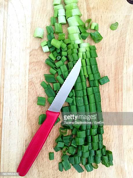 Close-Up Of Chopped Spring Onions With Kitchen Knife On Cutting Board