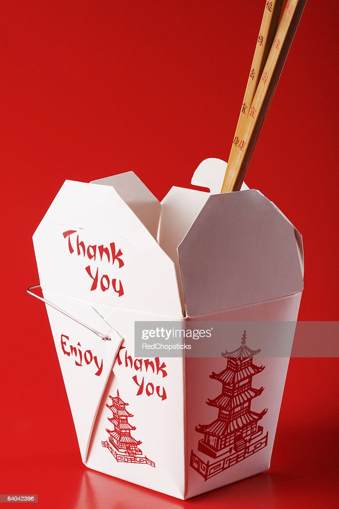 Close-up of chopsticks in a Chinese takeout box