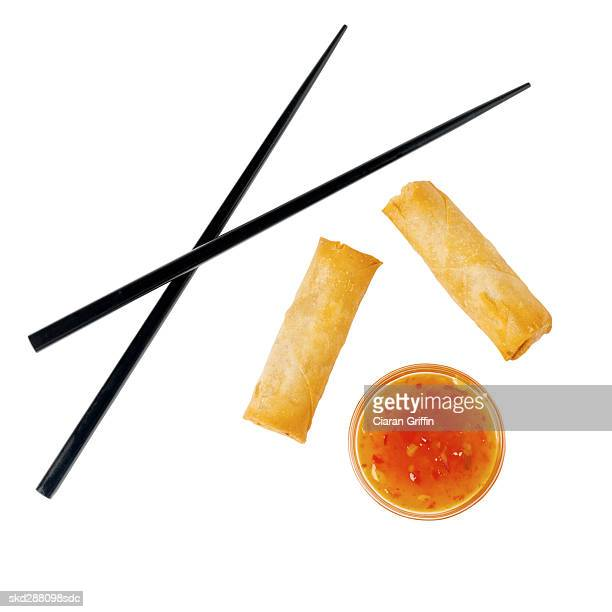 Close-up of chopsticks with spring rolls and dip