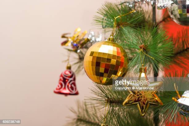 Close-Up Of Christmas Decoration On Christmas Tree with with Baubles, Stars and Christmas gifts