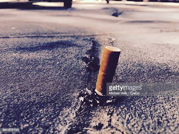 Close-Up Of Cigarette Butt On Road