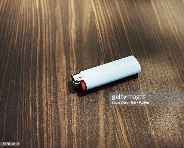 Close-Up Of Cigarette Lighter On Wooden Table
