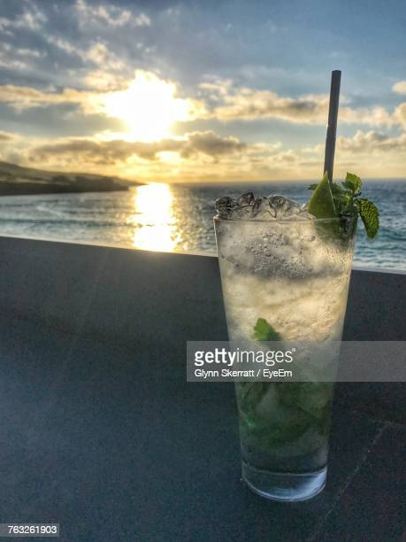 Close-Up Of Cocktail On Table Against Sea During Sunset