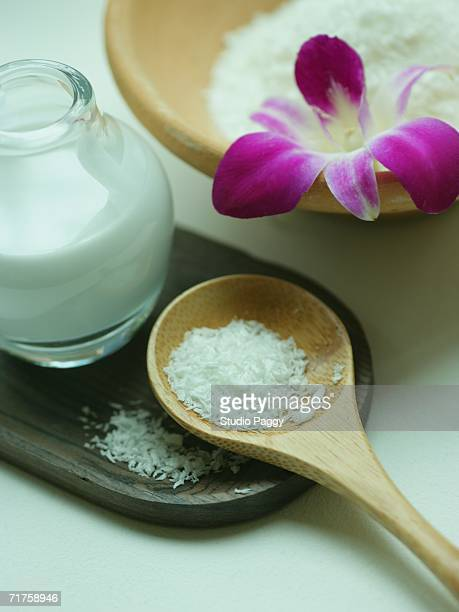 Close-up of coconut milk and powder with an orchid