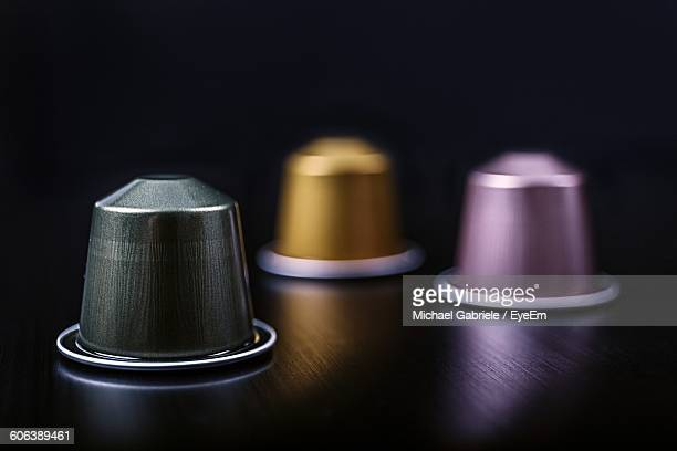 Close-Up Of Coffee Capsules On Table Against Black Background