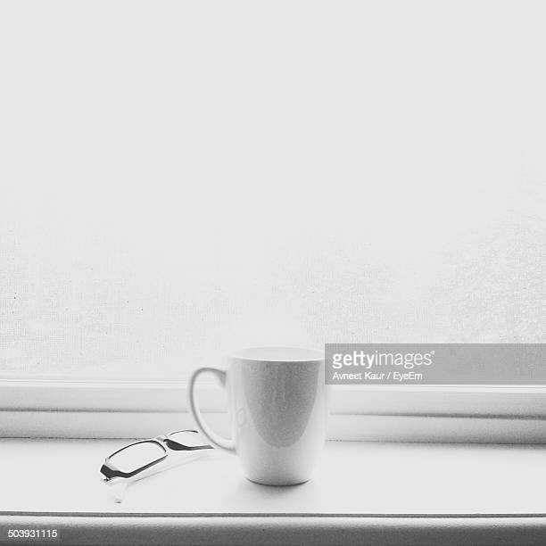 Close-up of coffee cup and glasses on window sill