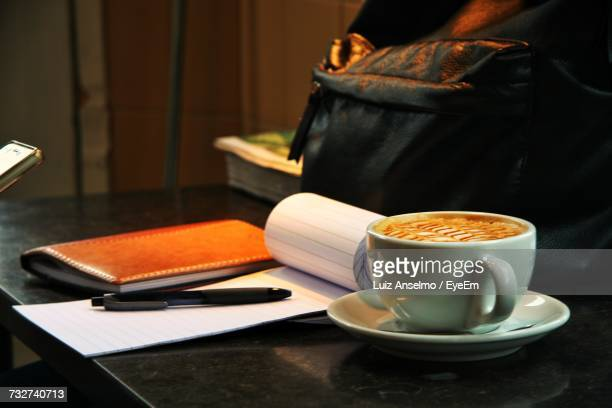 Close-Up Of Coffee Cup And Note Pad On Table