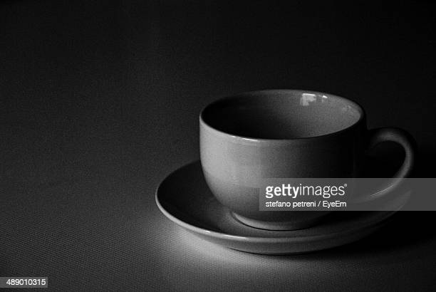 Close-up of coffee cup and saucer against dark background