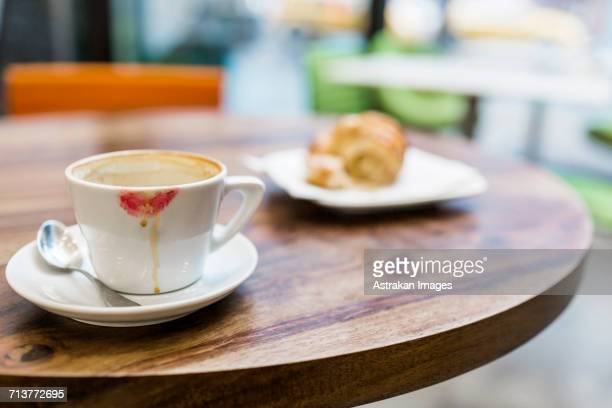 Close-up of coffee cup with lipstick kiss and croissant on table