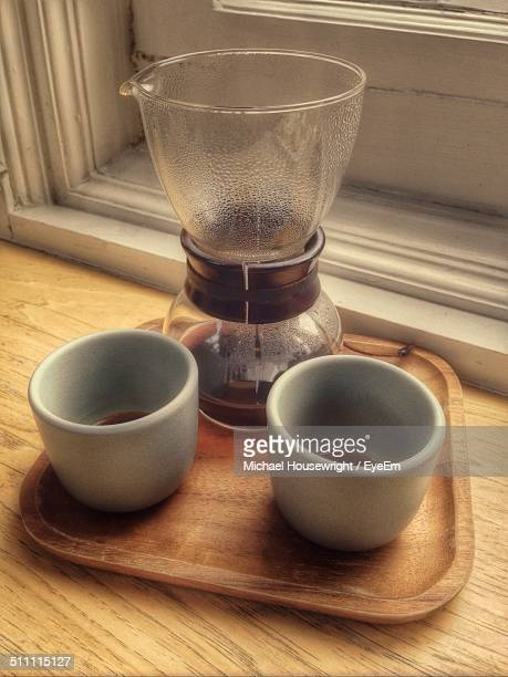 Close-up of coffee cups with grinder in serving tray
