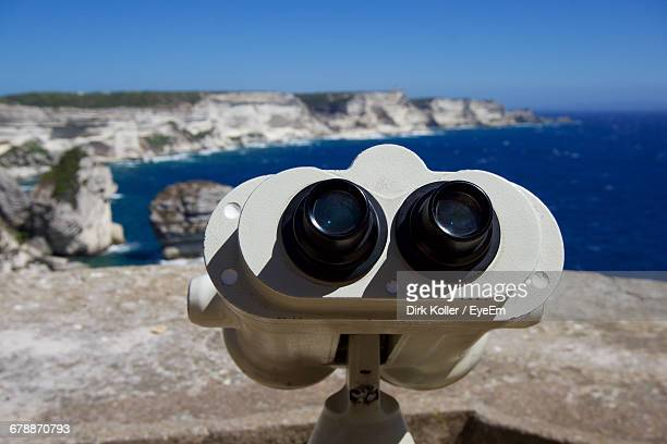Close-Up Of Coin-Operated Binoculars Against Sea And Rocky Shore