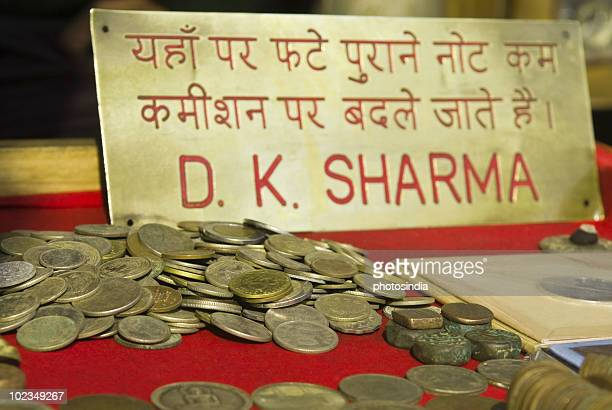 Close-up of coins at a money exchange stall, Delhi, India