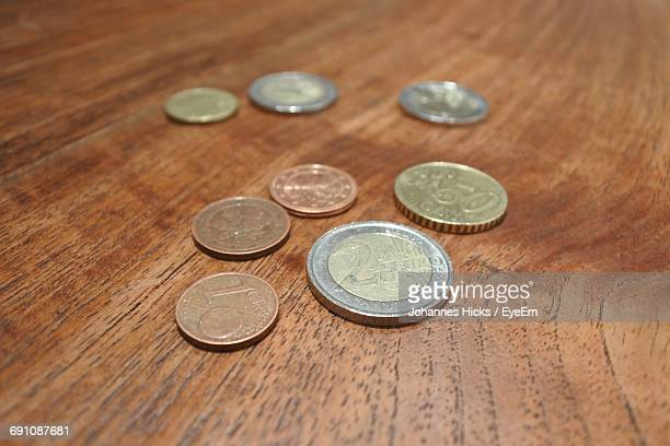Close-Up Of Coins On Wooden Table