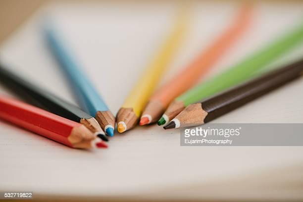 Close-up of color pencils and notebook