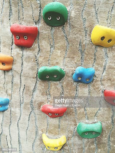 Close-Up Of Colorful Handgrips On Climbing Wall