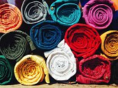 Close-up of colorful rolled jeans for sale