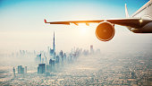 Close-up of commercial airplane flying over modern city. Concept of fast transportation and travel.