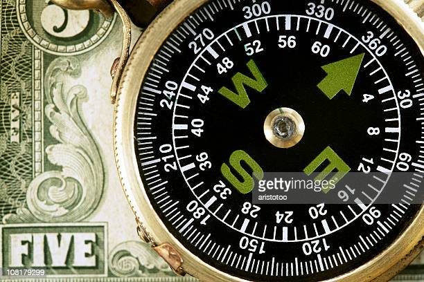 Close-up of Compass Lying on Five Dollar Bill
