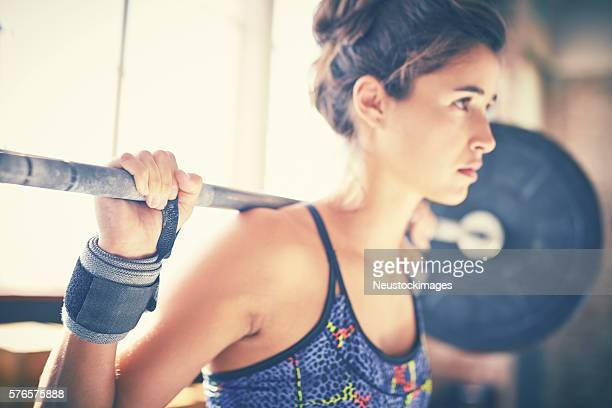 Close-up of confident woman exercising with barbell in gym