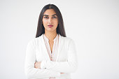 Closeup portrait of serious young pretty Indian business woman looking at camera and standing with arms crossed. Isolated front view on white background.