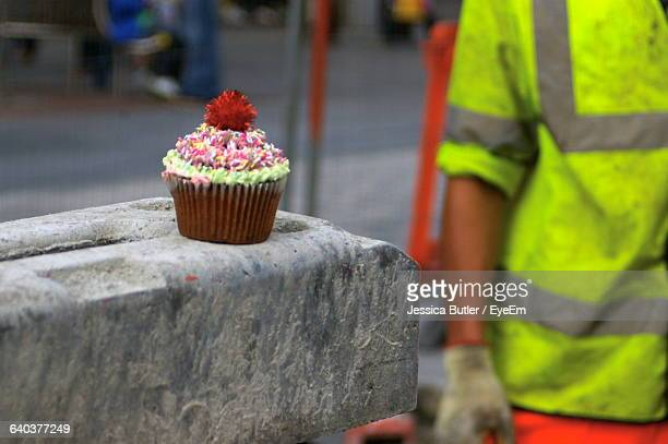 Close-Up Of Construction Worker With Cupcake On Rock