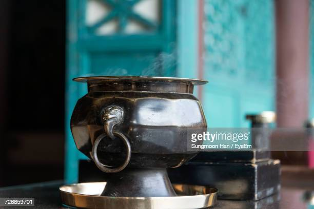 Close-Up Of Container On Table With Smoke At Temple