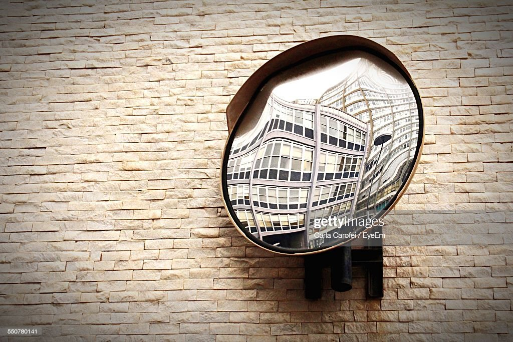 Close-Up Of Convex Mirror On Textured Wall