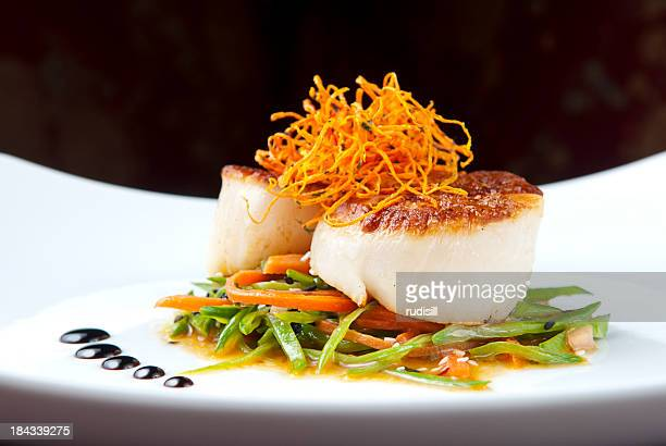 Close-up of cooked scallops on bed of vegetables