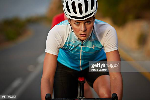 Close-up of cool female pro cyclist riding
