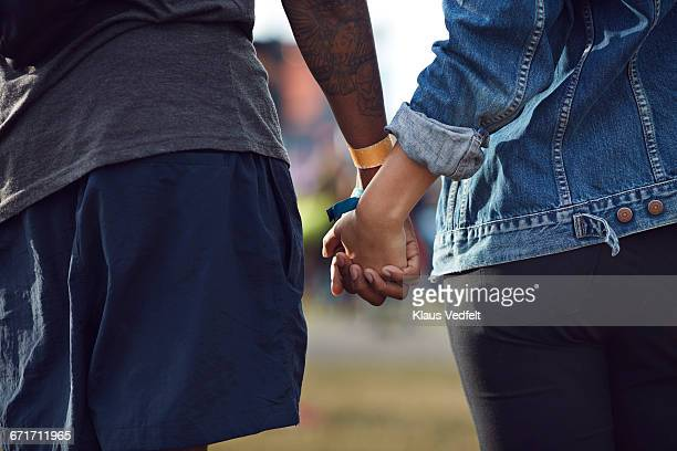 Close-up of couple holding hands at festival