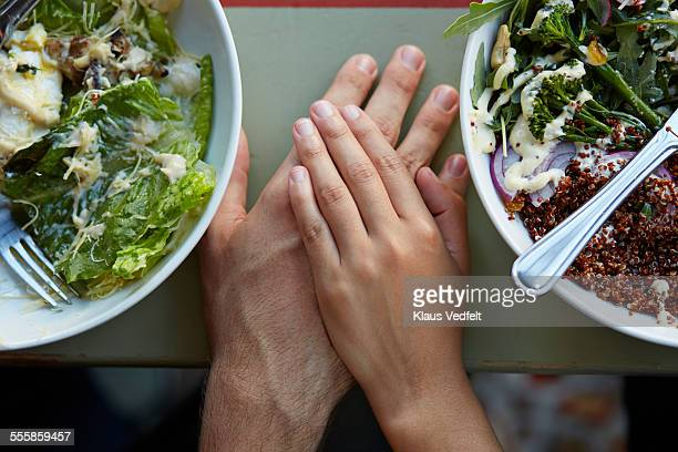 Close-up of couple holding hands at lunch