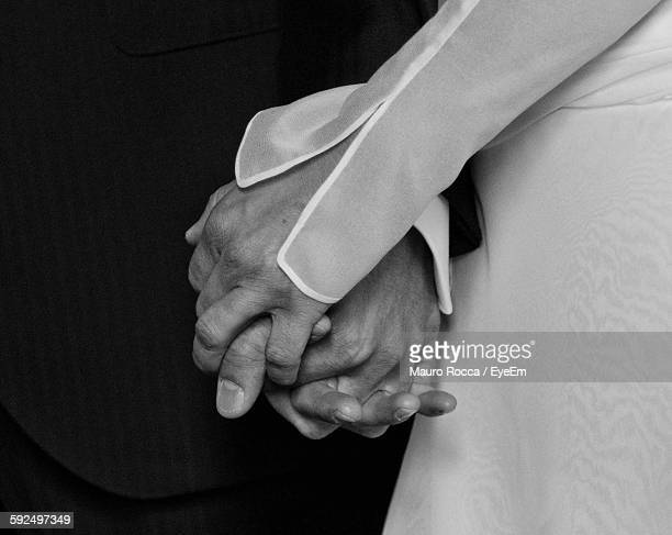 Close-Up Of Couple Holding Hands At Wedding