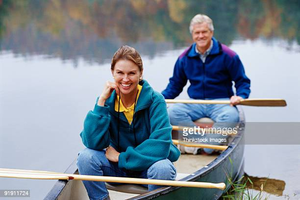Close-up of couple sitting in canoe, both with paddles in laps