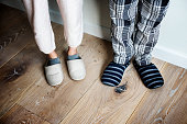 Closeup of couple wearing slippers on wooden floor