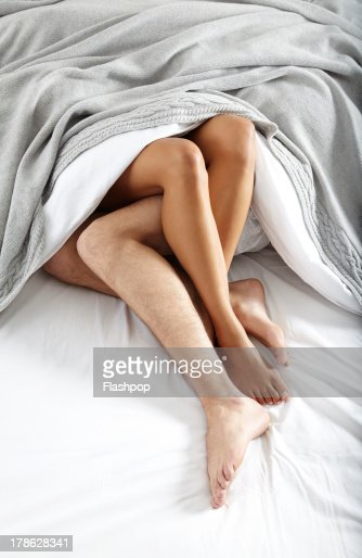 Close-up of couple's legs in bed together