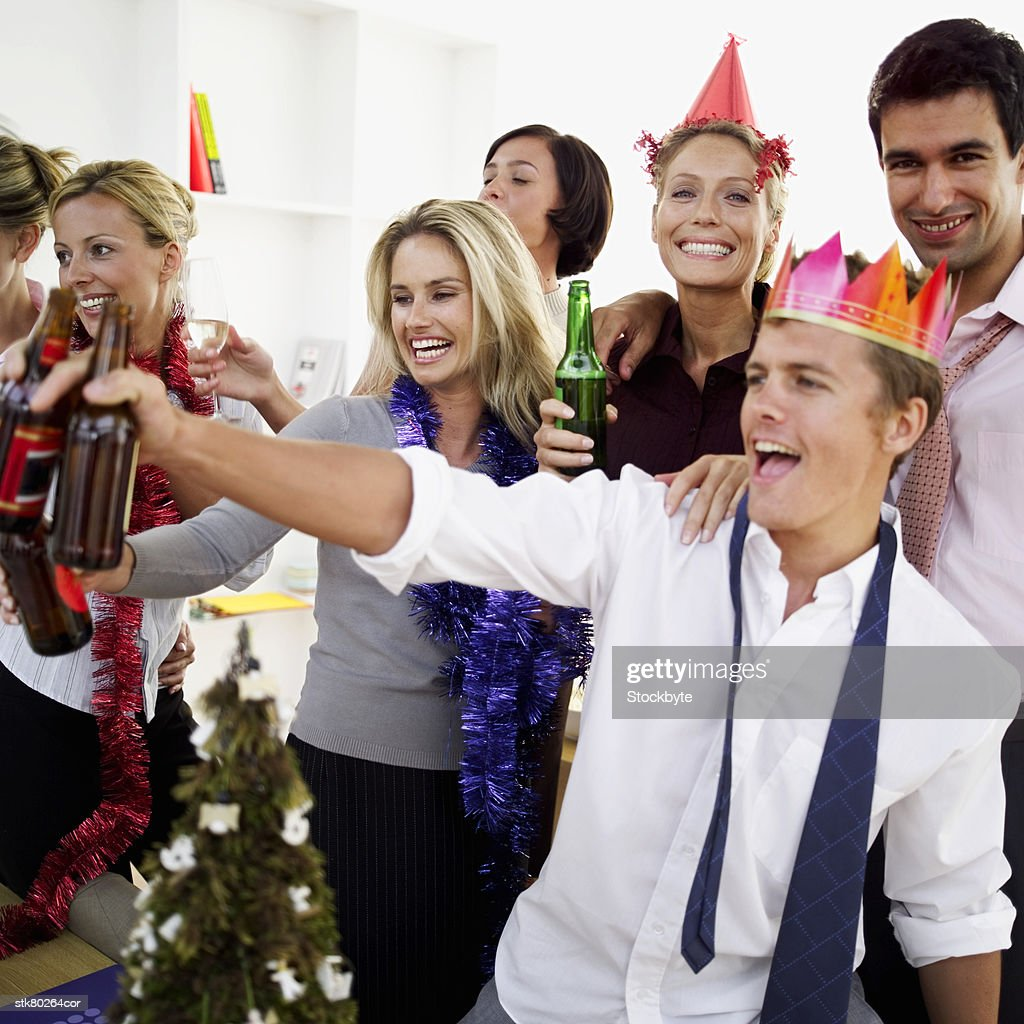 close-up of co-workers celebrating with beers at a office party : Stock Photo